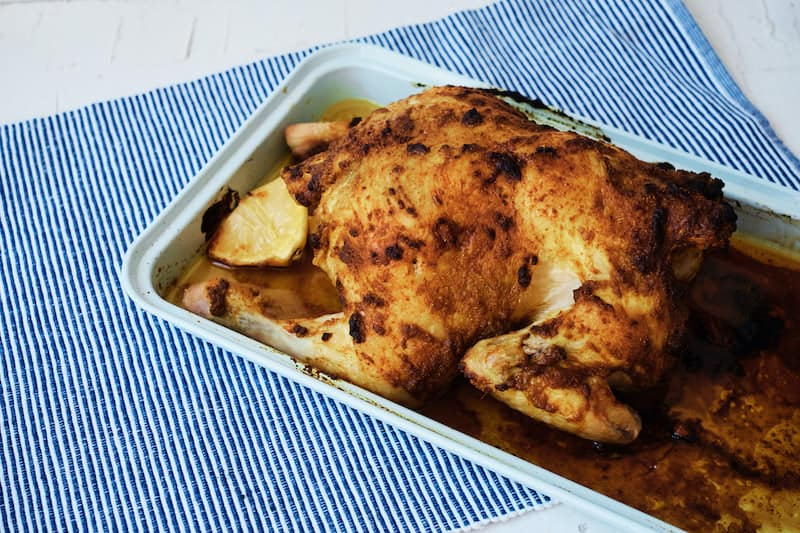 Whole roast chicken with Moroccan spices on a blue table cloth.