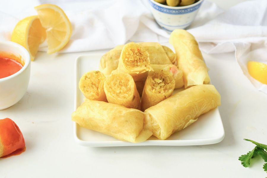 Stacked Moroccan briouats wrapped in a cigar shape with lemons and dipping sauce in the background