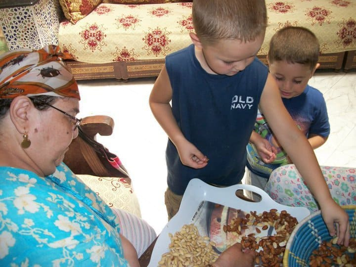Boys helping grandma shell almonds