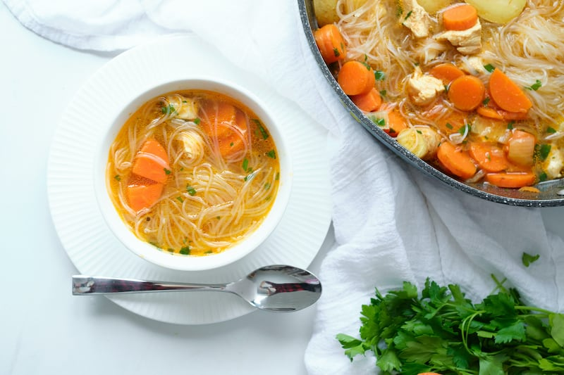 A large pot of soup in the right corner and a small single serve bowl in the main area of the image.