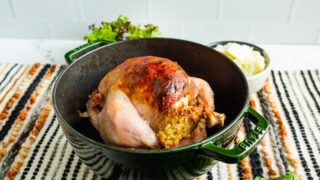 A cooked chicken sitting in a green roasting pot.
