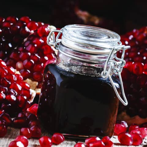 Glass bottle of pomegranate syrup with a flip top lid in the front of the image and cut open pomegranates in the background.