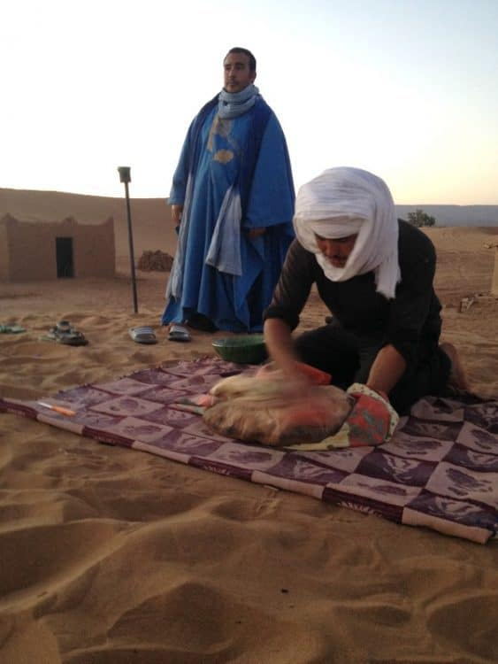 Cleaning off bread in the Sahara Desert