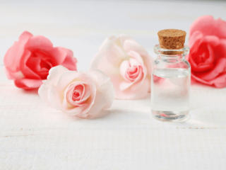 Vial of Rose Water with 4 pink roses behind it.