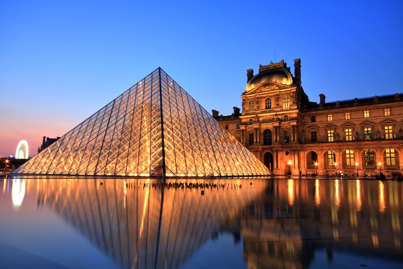 Louvre Pryramid lit up at night in Paris France