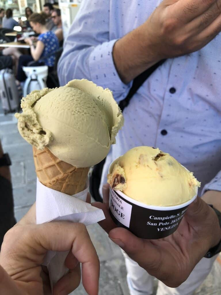 A man\'s hand holding a cup of nougat gelato. A woman\'s hand holding a cone of pistachio gelato.