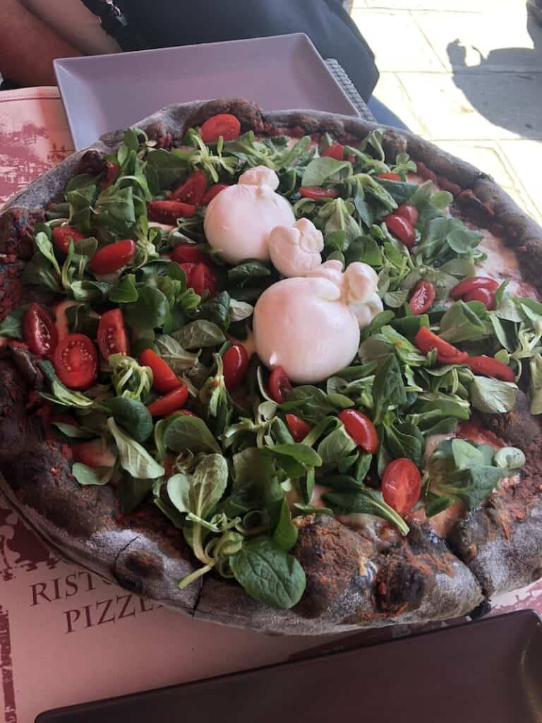Vegetarian pizza with a black crust at a restaurant in Burano Italy.
