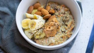 White bowl of carrot cake flavored oatmeal topped with bananas, almonds and peanut butter