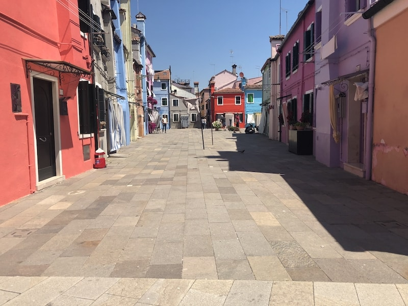 A pedestrian street in Burano Italy with brightly colored buildings on either side in violet, blues, and pinks.