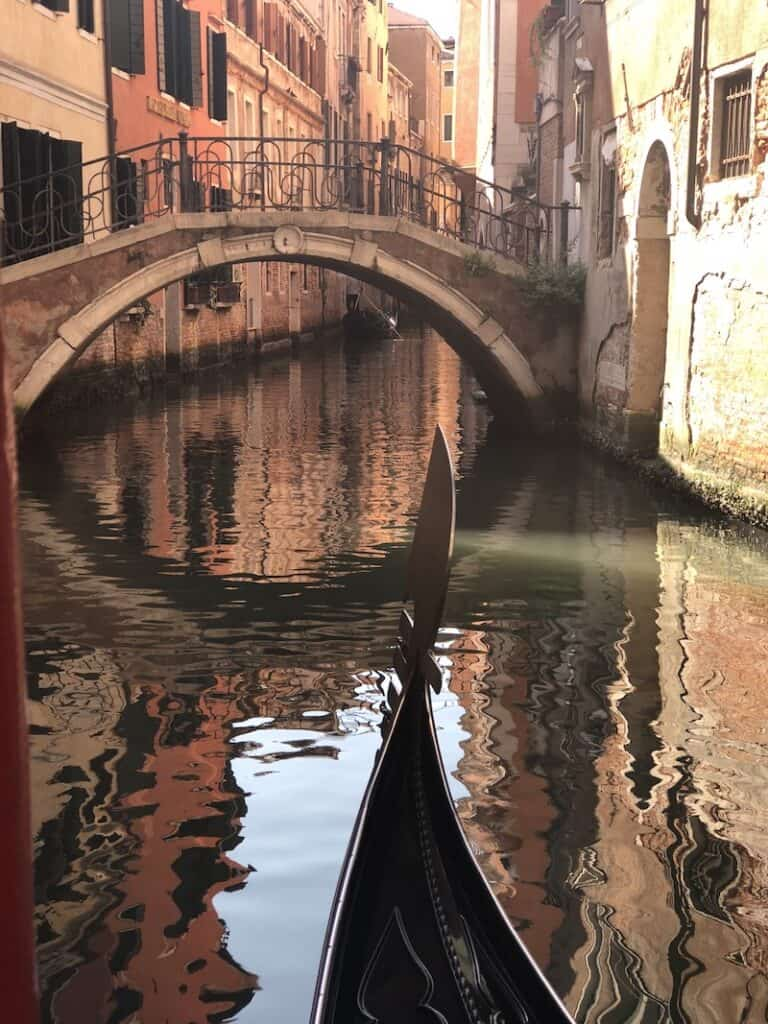 A gondola gliding on the water in Venice with a bridge to the front and just the tip of the boat visable in the image.
