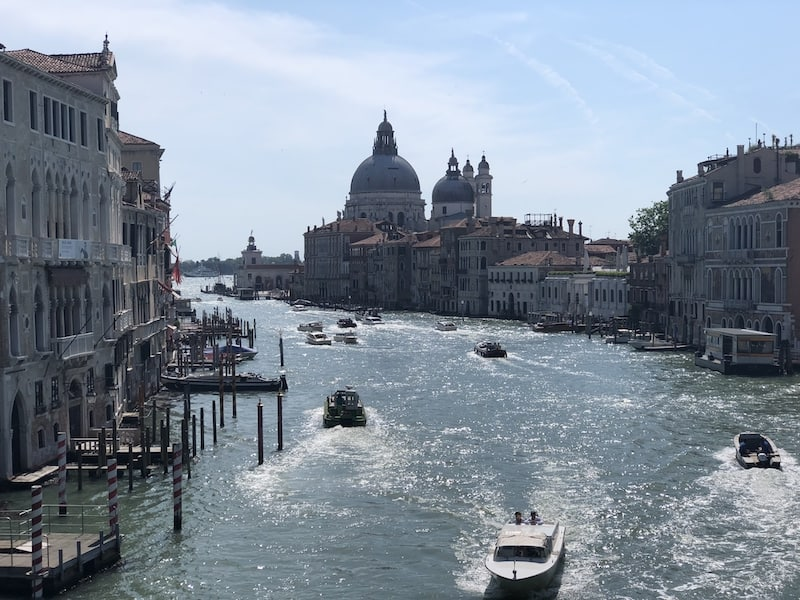 View from on top of a bridge looking towards the Grand Canal of Venice. There are several speed boats on the water below with buildings and docks to either side of the canal.