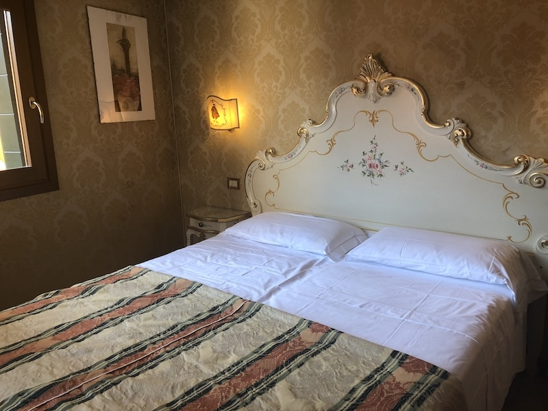 Hotel room in Venice with a queen bed that has a scroll headboard and white sheets.