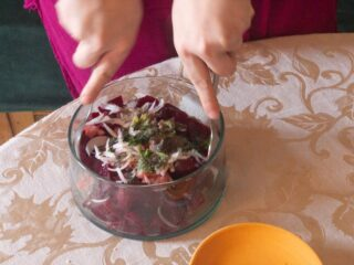 Two hands with spoons mixing beet salad in a large glass bowl.