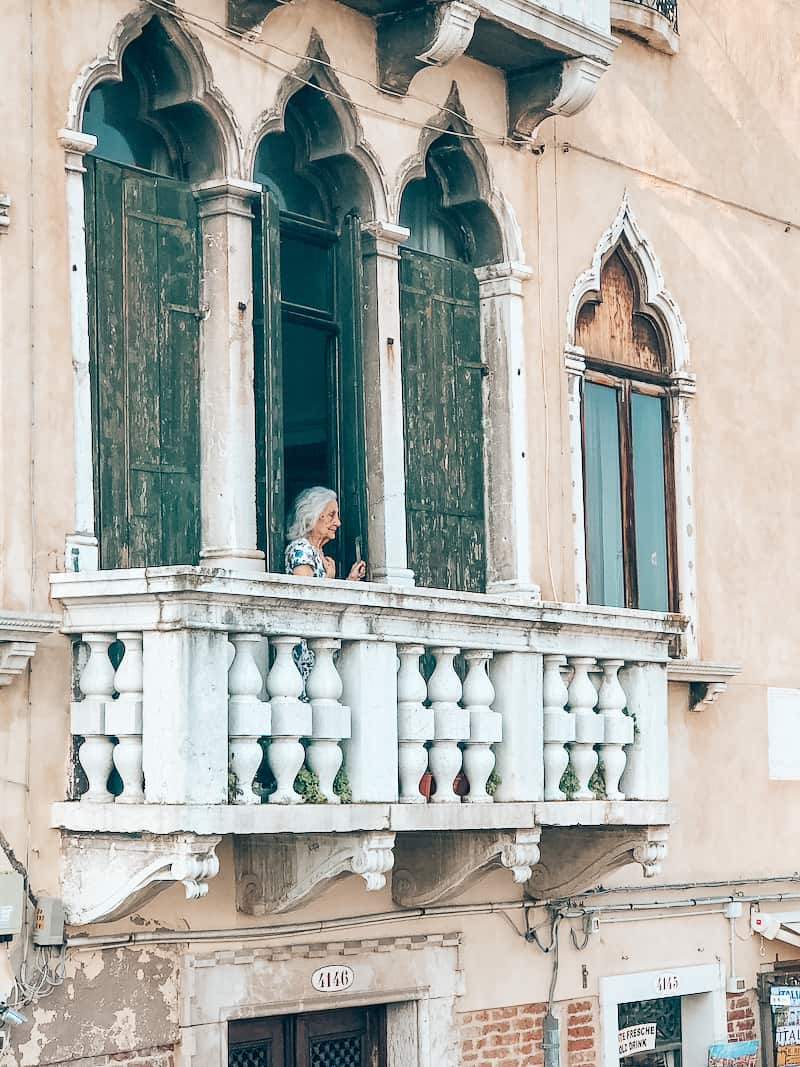 A white balcony off of an ivory building that has paint peeling. An thin, elderly woman with gray shoulder length hair looks off the balcony at the Grand Canal with her hands on the balcony railing.
