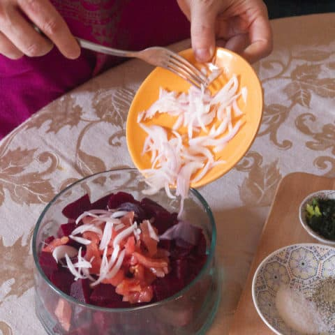 Adding sliced onions to a bowl of cooked beets.