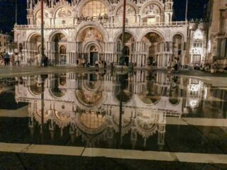 St. Mark's Cathedral at night is reflected in the water that has risen in the square from the high tide in Venice.