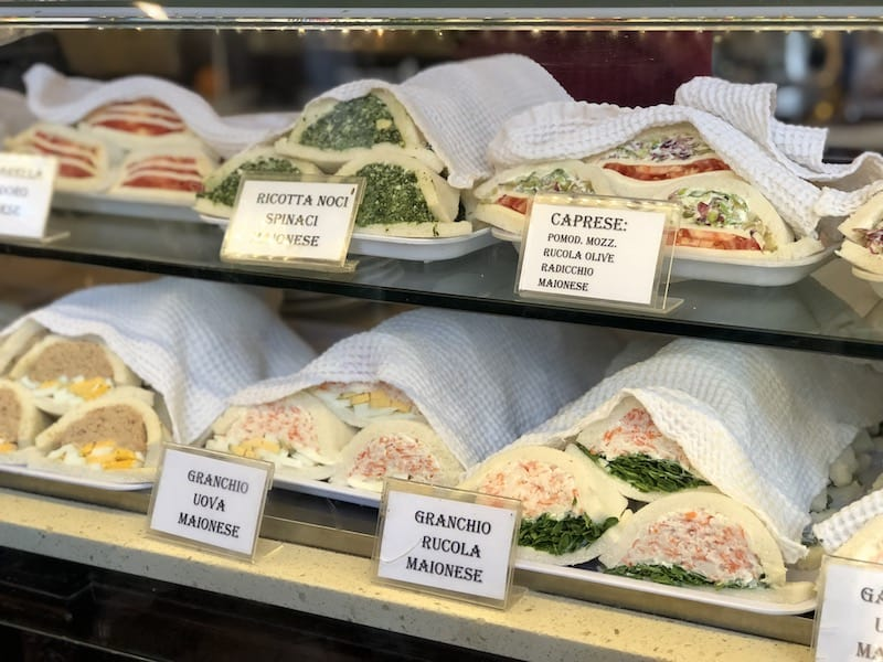 Two rows of traditional Venetian sandwiches in a bakery case. The sandwiches are soft white bread with one end open so the inside fillings are visible.