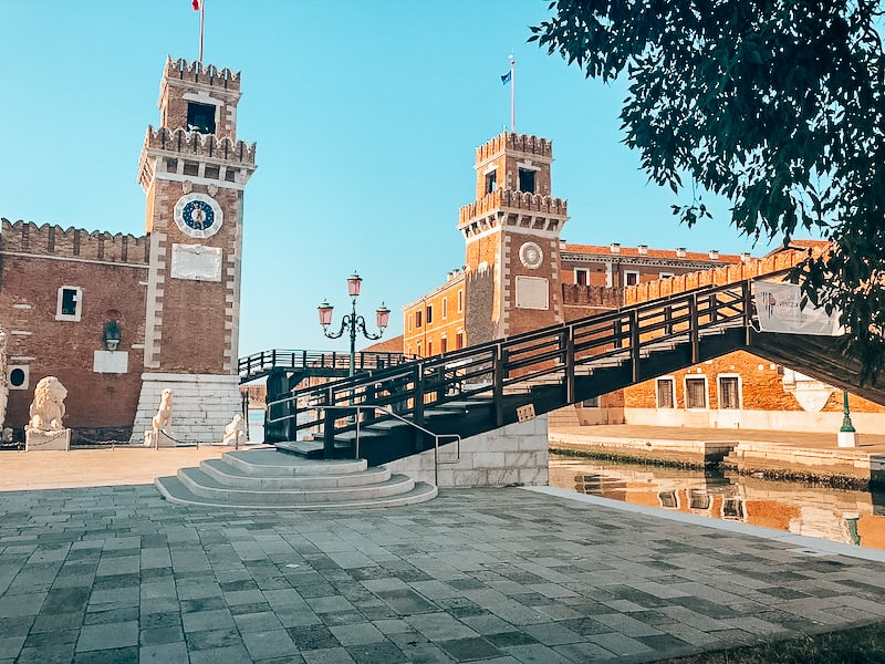 The Venice Naval Arsenal with a two tower buildings on either side of the image. A bridge crosses a canal directly in front of the buildings. A large statue of a lion is to the left of the image.