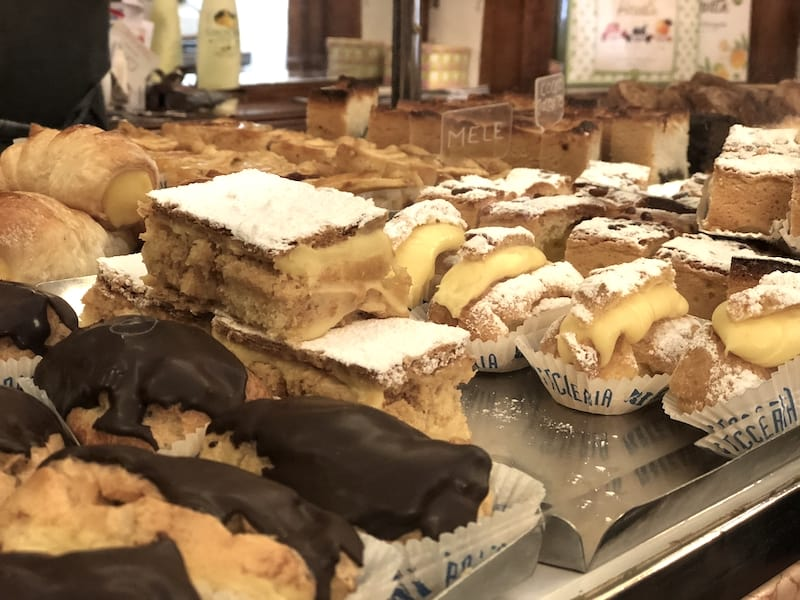 Bakery case with a variety of mixed Italian pastries including chocolate covered pastry, cream puffs, and cake slices.