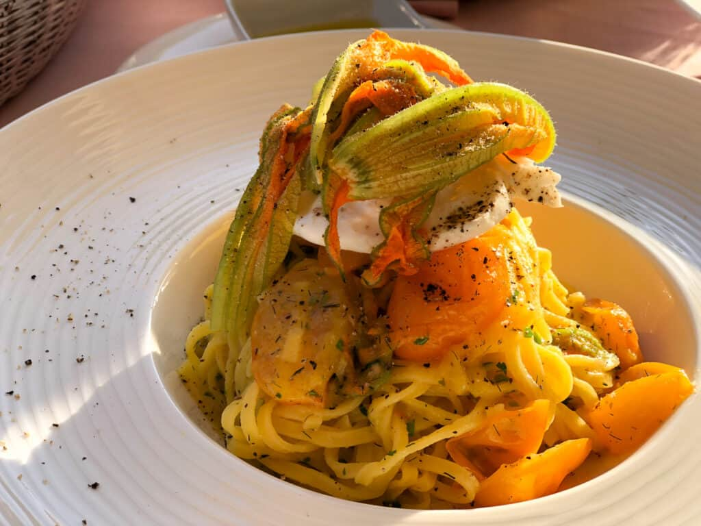 A large white bowl with a wide brim and small center area. Long spaghetti noodles are inside and topped with burrata cheese, zucchini flowers roasted tomatoes.