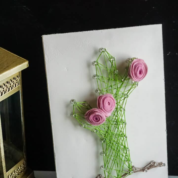 String Art Cactus Creation with Pink Roses. A lantern and string of beads are to the side of the craft.