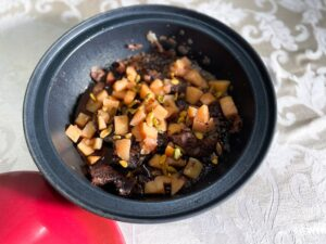 Bottom of a Black Tagine with cooked beef and quince inside