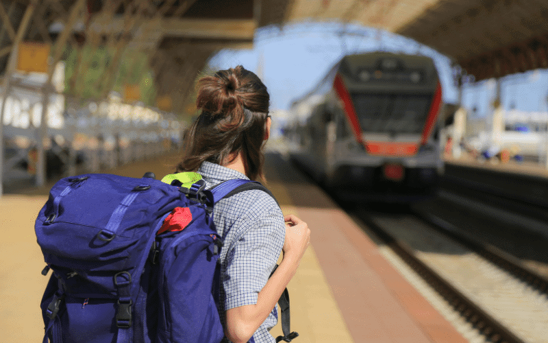 Brown haired girl waits in the foreground for a train. She has a purple backpack and is looking away from the camera.