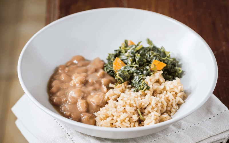 White bowl with cooked beans, white rice and green spinach