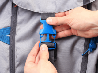 A grey backpack with blue snaps. Hands are snapping the middle snap.