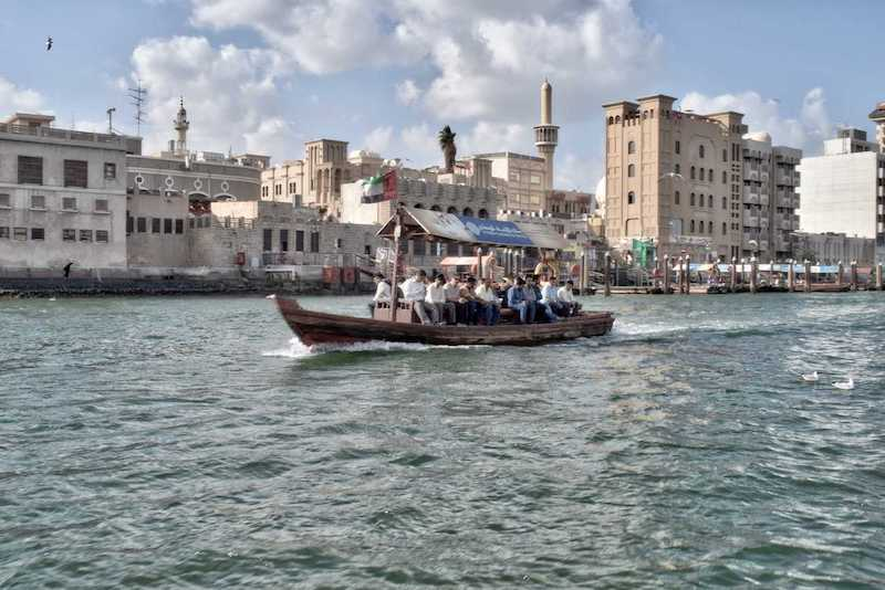 A traditional Abra boat goes down the Dubai Creek with buildings behind it