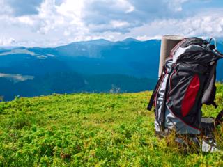 A grey and red backpack sits on a green mountaintop