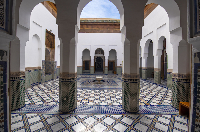 Courtyard of a Moroccan building with two white pillars in the foreground and blue and white tiled floor.