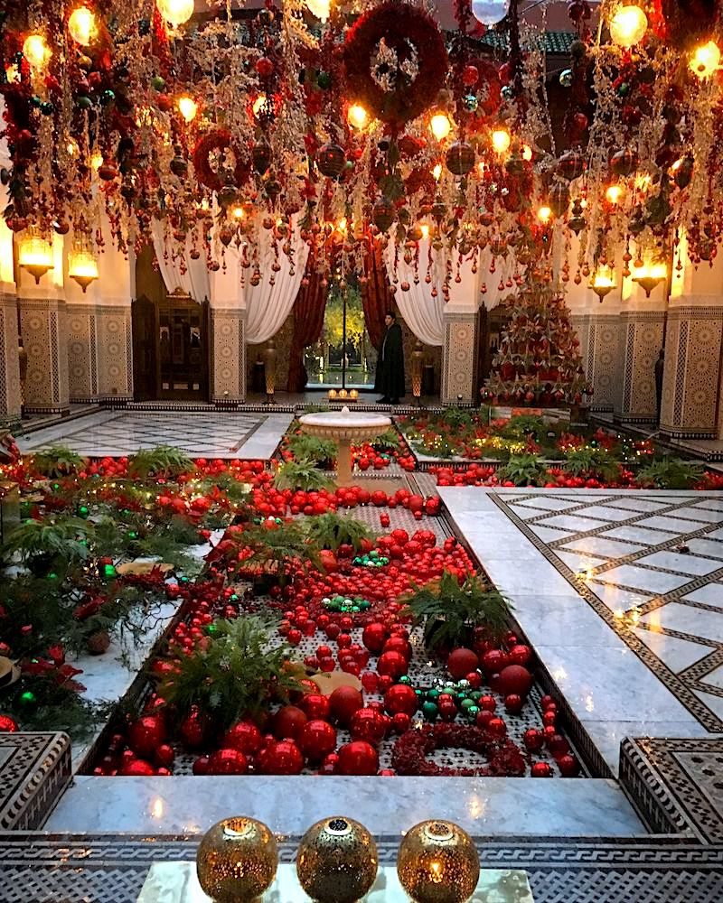 Red Christmas decorations in a Moroccan courtyard with a central pool.