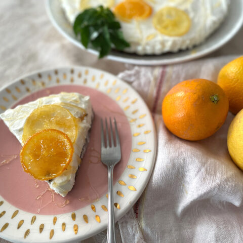 Slice of cheesecake on a pink plate with oranges and lemons to the side. It has sliced oranges on top.
